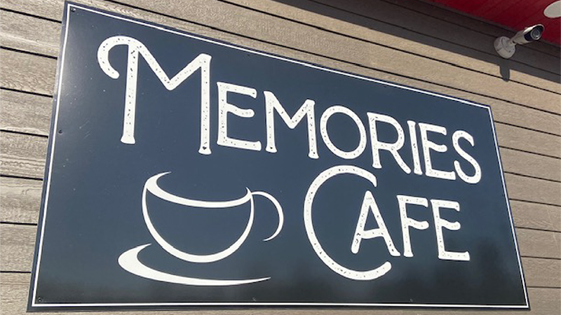 Memories Cafe sign with a coffe cup icon